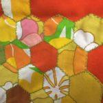 Retro quilted wandkleed poes in oranje en groen uit de jaren 1950