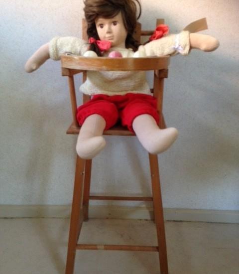 Handgemaakt poppenkind met vlechtjes in het pruikje
