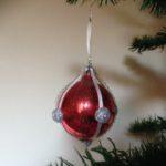 Oude rode kerstbal versierd met band, draad en glitterknopjes