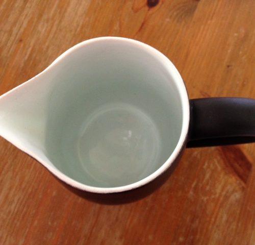 Retro melkkannetje in zwart plateel uit de fifty's