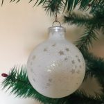 Oude antieke kerstbal van dun geblazen glas wit met sterretjes en plastic dopje.