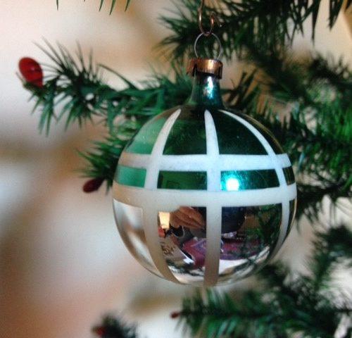 Oude antieke retro kerstbal van dun glas in zilver met groen, witte ruit uit de fifty's