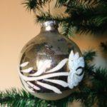 Oude kerstbal van glas uit de seventies met florale decoratie van witte verf