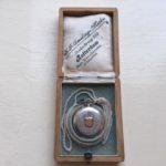 Antiek Zwitsers zilveren dames zakhorloge met gouden decoratie aan collier in houten  etui