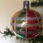 Oude antieke veelkleurige retro krater kerstbal van dun geblazen glas uit de fifty's
