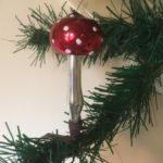 Antieke oude kerstbal een paddenstoel met rode hoed  op veer